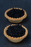 Tartlets with black caviar on a dark background Royalty Free Stock Image
