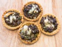 Tartlets com cogumelos e queijo no fundo de madeira Fotografia de Stock