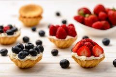 Tartlets com creme, mirtilos, framboesas e morangos na tabela de madeira branca Foco seletivo Foto de Stock