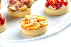 Tartlets com frutos e bagas em um close-up da placa em um fundo branco isolado fotografia de stock royalty free