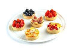 Tartlets com frutos e bagas em uma placa redonda em um fundo branco isolado fotografia de stock