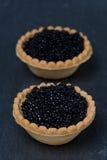 Tartlets con el caviar negro en un fondo oscuro imagen de archivo libre de regalías