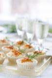Tartlets con el queso cremoso y el cierre rojo del caviar para arriba Bocados con el caviar rojo con el aperitivo Fondo ligero Fotos de archivo libres de regalías