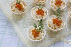 Tartlets con el queso cremoso y el cierre rojo del caviar para arriba Bocados con el caviar rojo con el aperitivo Fondo ligero Foto de archivo