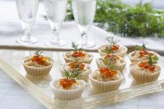 Tartlets con el queso cremoso y el cierre rojo del caviar para arriba Bocados con el caviar rojo con el aperitivo Fondo ligero Imagen de archivo