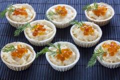 Tartlets con el queso cremoso y el cierre rojo del caviar para arriba en el fondo negro Fotos de archivo libres de regalías