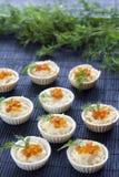 Tartlets con el queso cremoso y el cierre rojo del caviar para arriba en el fondo negro Fotos de archivo