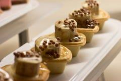 Tartlets con las rebanadas de la crema y del plátano debajo de la salsa dulce fotos de archivo