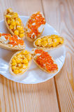 Tartlets with corn and red caviar Stock Images