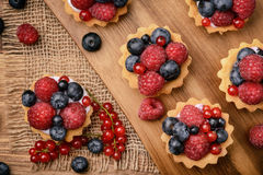 Tartlets with cream, blueberries, raspberries and red currants on brown wooden background. Top view. Royalty Free Stock Photo