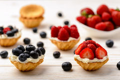 Tartlets with cream, blueberries, raspberries and strawberries on white wooden table. Selective focus. Tartlets with cream, blueberries, raspberries and Stock Photo