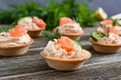 Tartlets with cream cheese and salted salmon on a wooden background. Tasty light snack for a party. Finger Food royalty free stock image