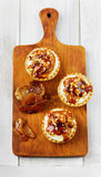 Tartlets with cream and nuts poured with caramel. From baked apples and brown sugar on a brown kitchen board Royalty Free Stock Photos