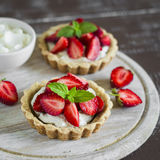 Tartlets with cream and strawberries, decorated with mint leaves Stock Image