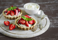 Tartlets with cream and strawberries, decorated with mint leaves Stock Images