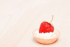 Tartlets with cream and strawberries on a light table, side view Stock Images