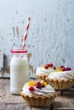 Tartlets de la torta dulce con las frutas, las bayas y la proteína poner crema con leche en un fondo de madera rústico imagen de archivo libre de regalías