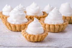 Tartlets do Shortcrust com doce e merengue italiana no branco foto de stock