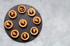 Tartlets dulces con el chocolate y las rebanadas de mandarina en un plato de la pizarra natural para servir, visión superior foto de archivo libre de regalías