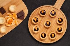 Tartlets dulces con el chocolate y las rebanadas de mandarina en un plato de madera para servir, visi?n superior imagen de archivo