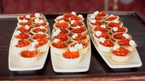 Tartlets enchidos com o caviar e o queijo creme vermelhos nas placas brancas vídeos de arquivo