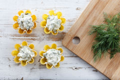 Tartlets filled with cheese and dill salad against rustic wooden background Royalty Free Stock Images