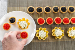 Tartlets filled with cheese and dill salad and caviar on bamboo placemat and a hand choosing tartlets to plate Stock Photography