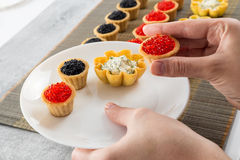 Tartlets filled with cheese and dill salad and caviar on bamboo placemat and a hand choosing tartlets to plate Stock Photos