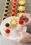 Tartlets filled with cheese and dill salad and caviar on bamboo placemat and a hand choosing tartlets to plate Royalty Free Stock Image