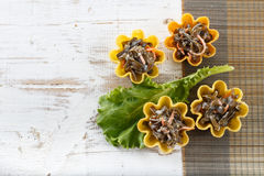 Tartlets filled with seaweed salad on bamboo placemat against rustic wooden background Stock Photos