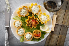 Tartlets filled with vegetables and cheese and dill salad on white plate and leaf against rustic wooden background Stock Photography