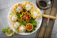 Tartlets filled with vegetables and cheese and dill salad on white plate and leaf against rustic wooden background Stock Image