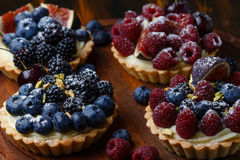 Tartlets with fresh berries on wooden background Royalty Free Stock Images