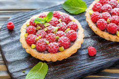 Tartlets with fresh raspberries and pistachios. Stock Image