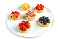 Tartlets with fruits and berries on an isolated white background royalty free stock photos
