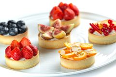 Tartlets with fruits and berries in a plate close-up on an isolated white background stock photos