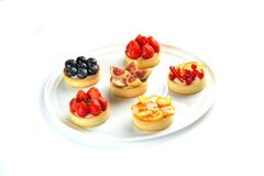 Tartlets with fruits and berries in a plate on an isolated white background stock image