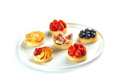 Tartlets with fruits and berries in a round plate on an isolated white background stock photo