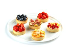 Tartlets with fruits and berries in a round plate on an isolated white background stock photography