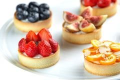 Tartlets with fruits and berries in a plate close-up on an isolated white background stock images