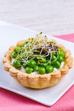Tartlets with green peas Stock Photos