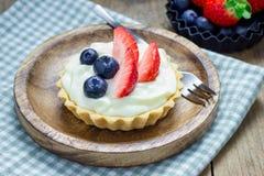 Tartlets hechos en casa de la torta dulce con crema, la fresa y el arándano de las natillas Foto de archivo