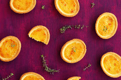 Tartlets with lemon filling and thyme on deep lilac background Stock Photo