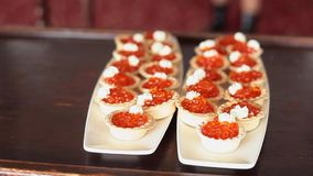Tartlets llenados del caviar y del queso cremoso rojos en las placas blancas almacen de video