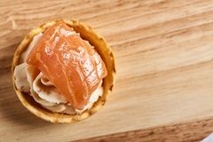 Tartlets with mascarpone and red fish on a wooden table. copyspace. Tartlets with mascarpone and red fish on a wooden table royalty free stock image