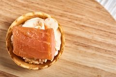 Tartlets with mascarpone and red fish on a wooden table. copyspace. Tartlets with mascarpone and red fish on a wooden table royalty free stock photos