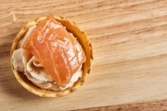 Tartlets with mascarpone and red fish on a wooden table. copyspace. Tartlets with mascarpone and red fish on a wooden table stock photography