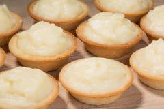 Tartlets mit Vanillepudding auf dem Tisch Lizenzfreie Stockfotos