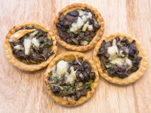 Tartlets with mushrooms and cheese on wooden background. Baked tartlets with mushrooms and cheese lying on wooden background Stock Photography