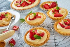 Tartlets och syrligt med jordgubbar, banan, mintkaramell arkivbilder